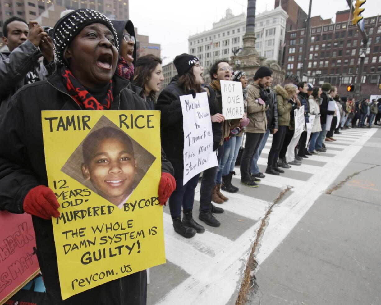 FILE - This Nov. 25, 2014, file photo, shows demonstrators blocking Public Square in Cleveland, during a protest over the police shooting of 12-year-old Tamir Rice. The family of 12-year-old Tamir Rice, who was shot and killed by Cleveland police in 2014, asked the Justice Department on Friday to reopen the case into the boy's death after it was closed in the waning weeks of the Trump administration.