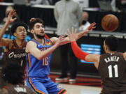 Oklahoma City Thunder guard Ty Jerome, center, passes as Portland Trail Blazers guard Anfernee Simons, left, and center Enes Kanter, right, defend during the first half of an NBA basketball game in Portland, Ore., Saturday, April 3, 2021.