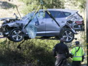 FILE - In this Feb. 23, 2021, file photo, a crane is used to lift a vehicle following a rollover accident involving golfer Tiger Woods, in the Rancho Palos Verdes suburb of Los Angeles. The Los Angeles County sheriff plans to announce Wednesday, April 7, 2021, what caused Woods to crash an SUV in Southern California earlier in the year, seriously injuring himself in the wreck. (AP Photo/Ringo H.W.