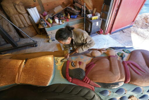 Lummi Nation lead carver Jewell Praying Wolf James works on the final details of a nearly 25-foot totem pole to be gifted to the Biden administration Monday on the Lummi Reservation, near Bellingham.