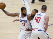 Los Angeles Clippers guard Paul George (13) holds the ball as Ivica Zubac (40) sets a screen on Portland Trail Blazers guard Damian Lillard, center, during the second half of an NBA basketball game Tuesday, April 6, 2021, in Los Angeles.