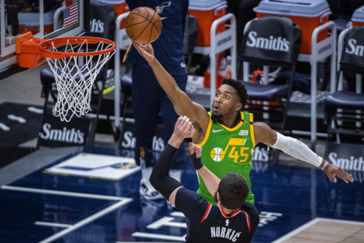 Utah Jazz guard Donovan Mitchell (45) lays the ball up while guarded by Portland Trail Blazers center Jusuf Nurkic (27) during the first half of an NBA basketball game Thursday, April 8, 2021, in Salt Lake City.