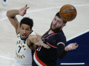 Indiana Pacers guard Malcolm Brogdon, left, and Portland Trail Blazers center Jusuf Nurkic reach for a rebound during the first half of an NBA basketball game in Indianapolis, Tuesday, April 27, 2021.
