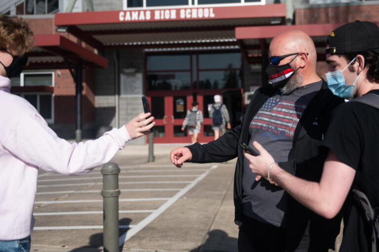 Camas High School staff member Dale Rule, center, checks health screeners on studentsÕ phones before they enter the building for class on Monday, April 19, 2021. Camas returned to four-day-a-week in-person instruction on Monday.