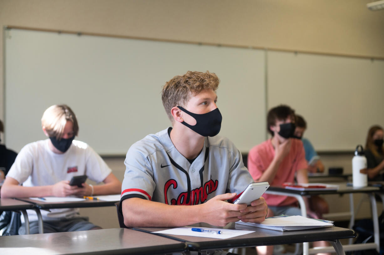 Lucas Warner, center, focusses during a calculus class taught by Craig Hardin at Camas High School on Monday. Camas returned to four-day-a-week in-person instruction on Monday.