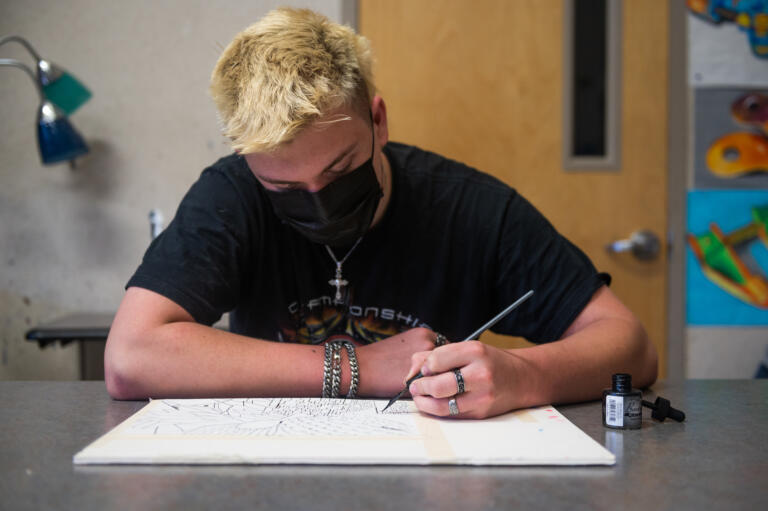 James Hatch works on a mixed media art piece in a class called ÔEverything in ArtÕ, taught by Rod Raunig, at Camas High School on Monday, April 19, 2021. Camas returned to four-day-a-week in-person instruction on Monday.