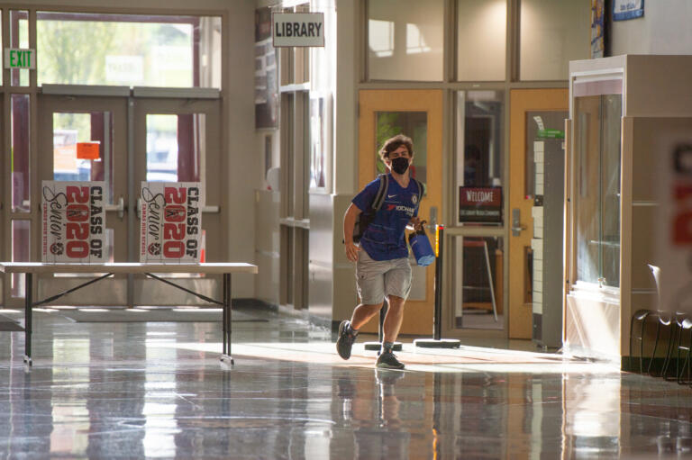 A student runs to class at Camas High School on Monday, April 19, 2021. Camas returned to four-day-a-week in-person instruction on Monday.