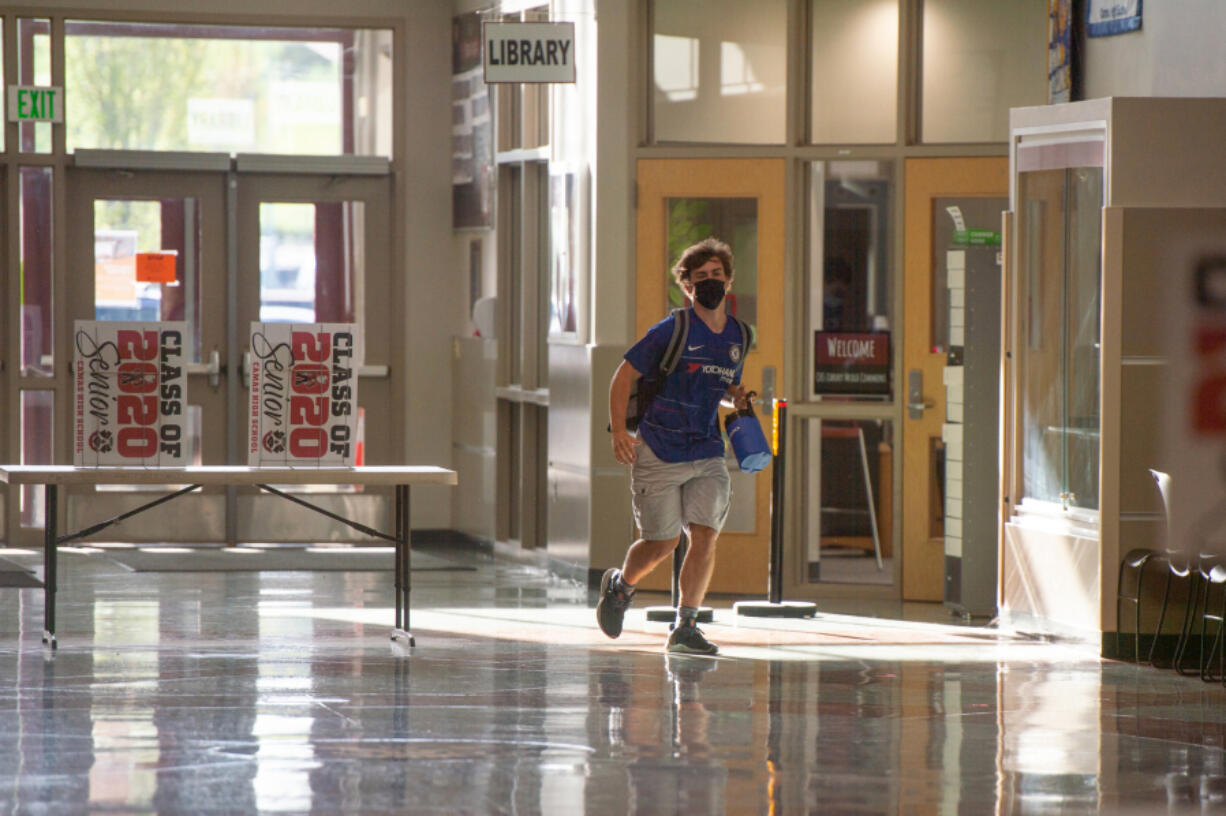 A student runs to class at Camas High School earlier this month after the district switched to in-person instruction four days a week. Officials said there has been no COVID-19 transmission in schools since the change.