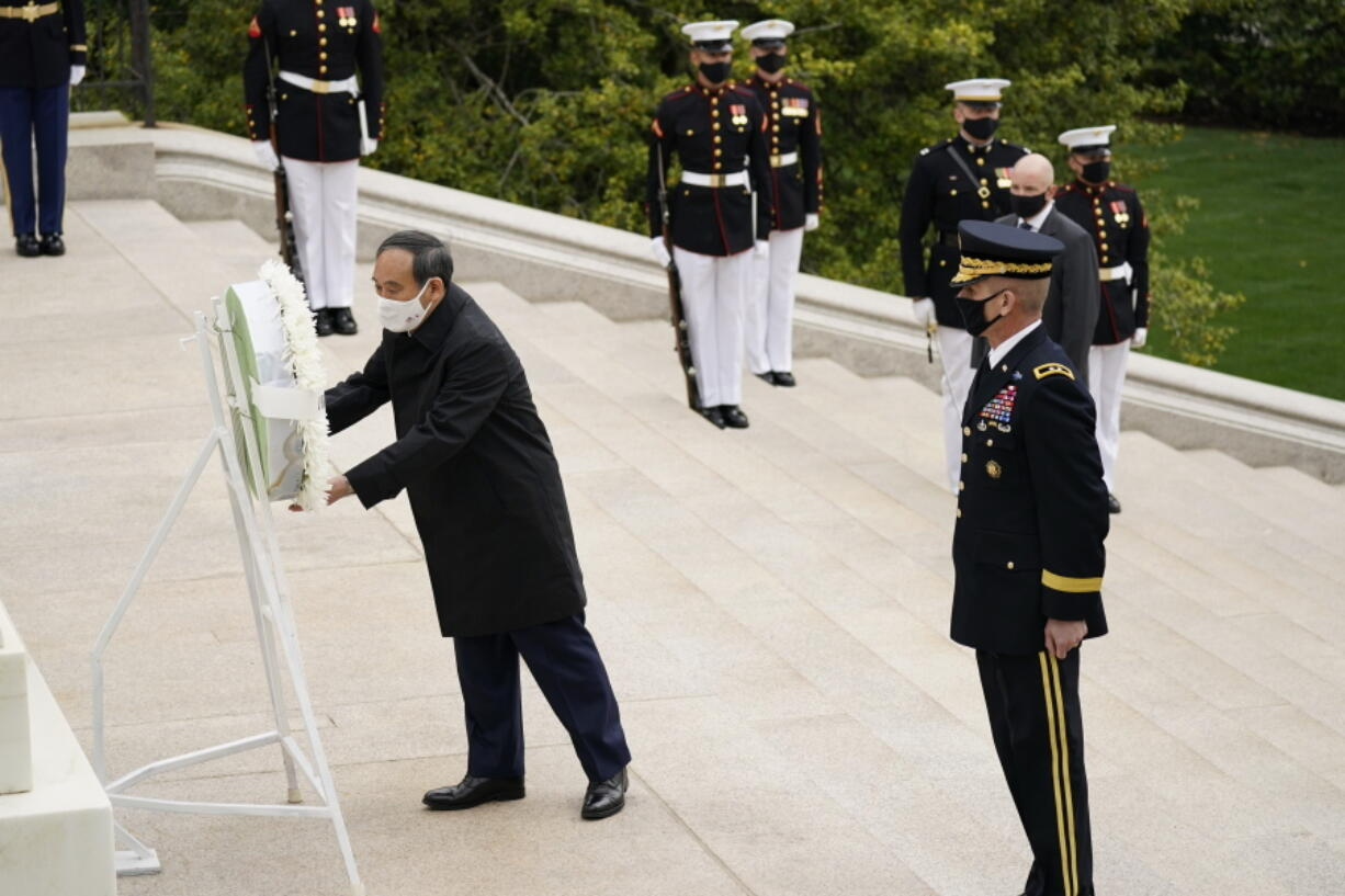 Japanese Prime Minister Yoshihide Suga places a wreath at the Tomb of the Unknown Soldier during a ceremony at Arlington National Cemetery in Arlington, Va., Friday morning, April 16, 2021, with U.S. Army Maj. Gen. Omar Jones.