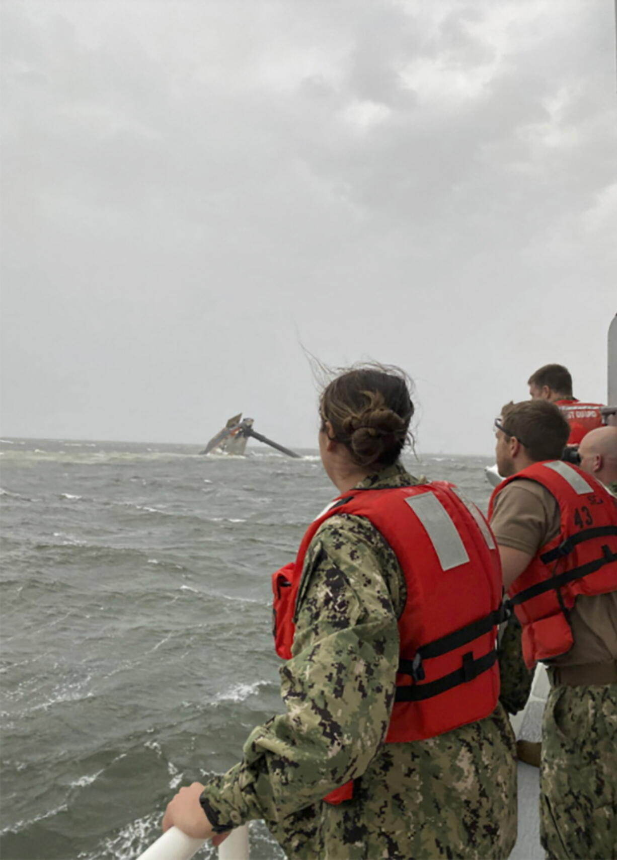 In this photo provided by the U.S. Coast Guard, crew members of the Coast Guard Cutter Glenn Harris scan the water while searching for those missing Tuesday, April 13, 2021, after a 175-foot commercial lift boat capsized 8 miles south of Grand Isle, La. The Seacor Power, an oil industry vessel, flipped over Tuesday in a microburst of dangerous wind and high seas. (U.S.