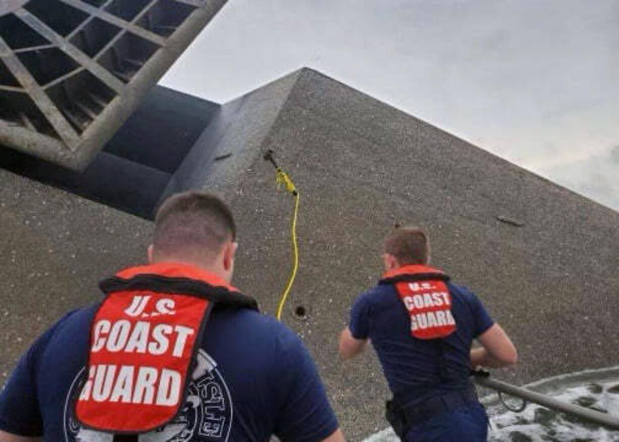In this photo provided by the U.S. Coast Guard, Coast Guard Station Grand Isle 45-foot Response Boat-medium boat crew members attempt to throw a hammer at the hull of the SeaCor Power. The crew was attempting to make contact with potential survivors inside the vessel. . The Seacor Power, an oil industry vessel, flipped over Tuesday, April 13, 2021 in a microburst of dangerous wind and high seas. (U.S.