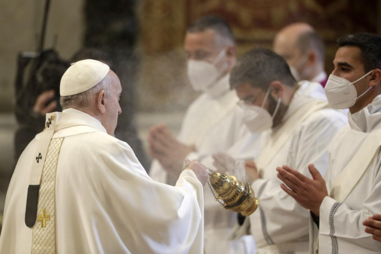 Pope Francis spreads incense during a ceremony to ordain nine new priests, standing in front of him and wearing face masks to curb the spread of COVID-19, inside St. Peter's Basilica, at the Vatican, Sunday, April 25, 2021.
