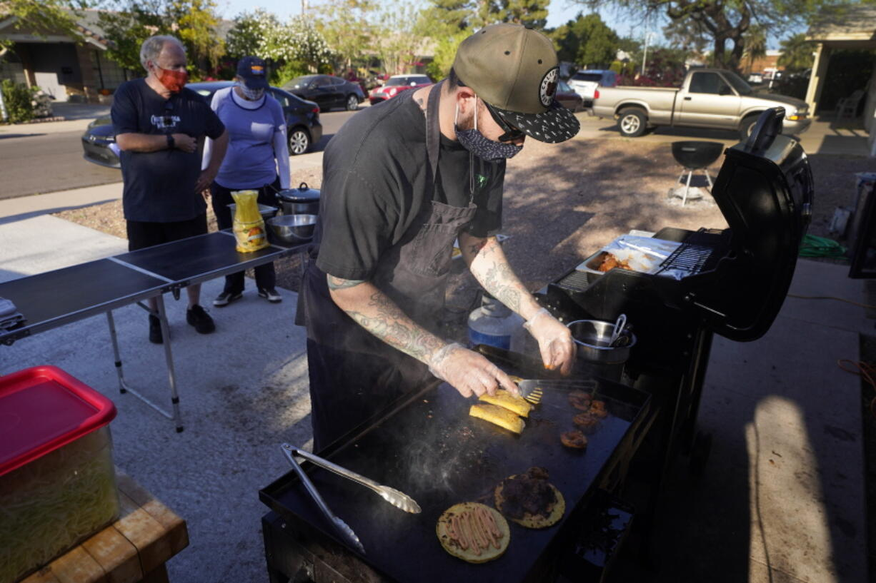 Chef Mike Winneker prepares tacos in front of his home Saturday, April 3, 2021, in Scottsdale, Ariz. Beaten down by the pandemic, many laid-off or idle restaurant workers have pivoted to dishing out food with a taste of home. Some have found their entrepreneurial side, slinging their culinary creations from their own kitchens. (AP Photo/Ross D.