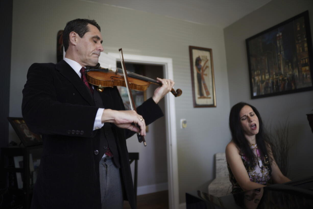 Musicians David Shenton and Erin Shields perform inside their home in the Queens borough of New York on March 30, 2021. The married couple have led virtual concerts from their living room to raise thousands of dollars for the Mosaic West Queens Church food pantry, where they volunteer every weekend.
