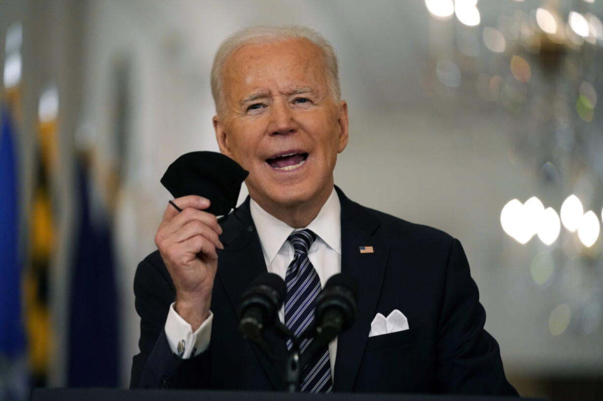 FILE - In this March 11, 2021, file photo, President Joe Biden holds up his face mask as he speaks about the COVID-19 pandemic during a prime-time address from the East Room of the White House in Washington. The U.S. is meeting President Joe Biden's latest vaccine goal of administering 200 million COVID-19 shots in his first 100 days in office, as the White House steps up its efforts to inoculate the rest of the public.