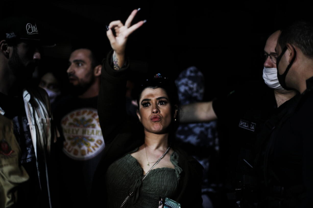 A woman flashes a V sign as police break up a social gathering during an operation against illegal and clandestine gatherings that authorities believe are partly responsible for fueling the spread of COVID-19, at a party hall in Sao Paulo, Brazil, early Saturday, April 17, 2021.