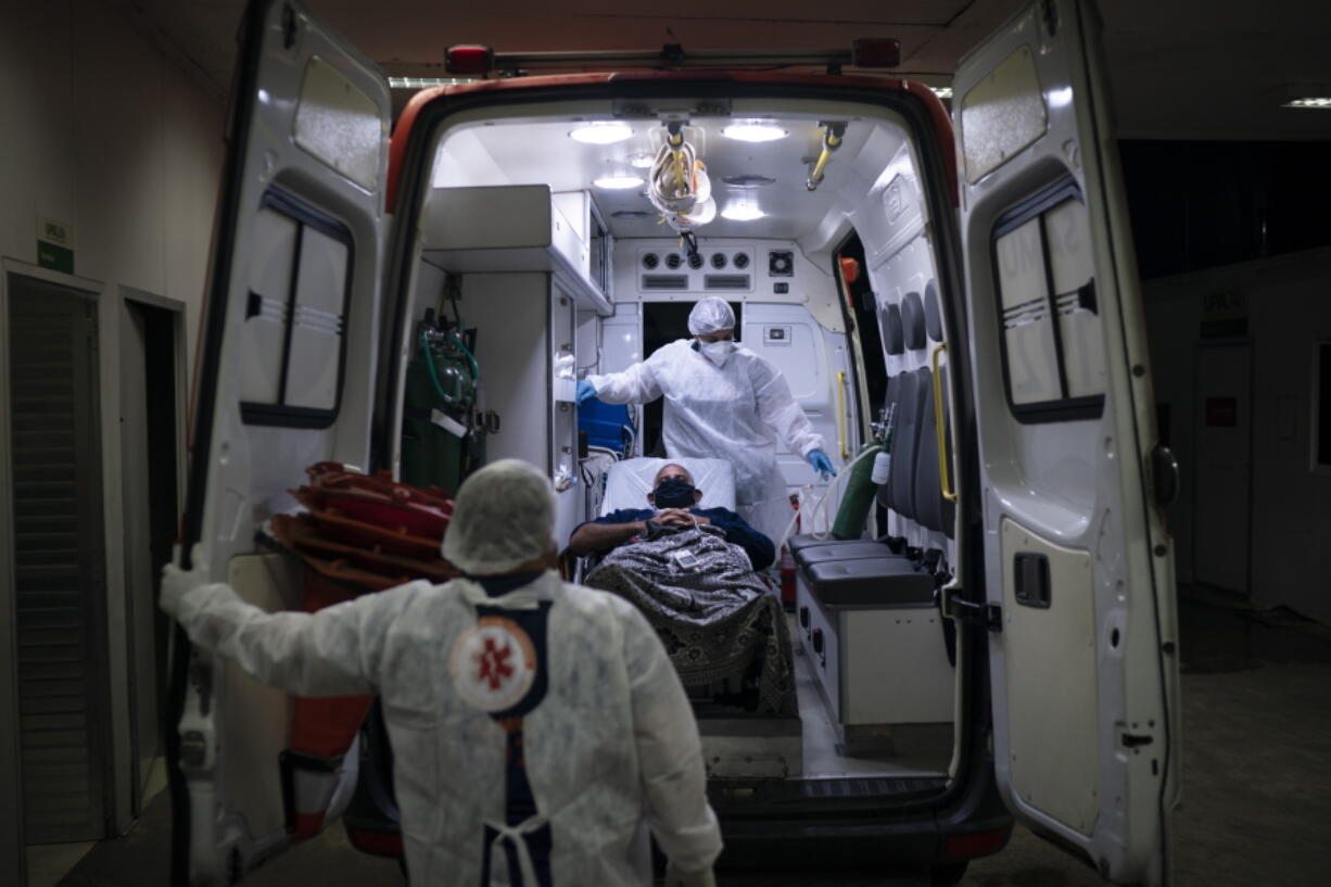 Mobile Emergency Care Service (SAMU) workers Gabrielle Carlos, top, and Joao Vericimo, move a COVID-19 patient to an ambulance as he is transferred to a municipal hospital dedicated to COVID-19 in Duque de Caxias, Rio de Janeiro state, Brazil, Tuesday, April 6, 2021.