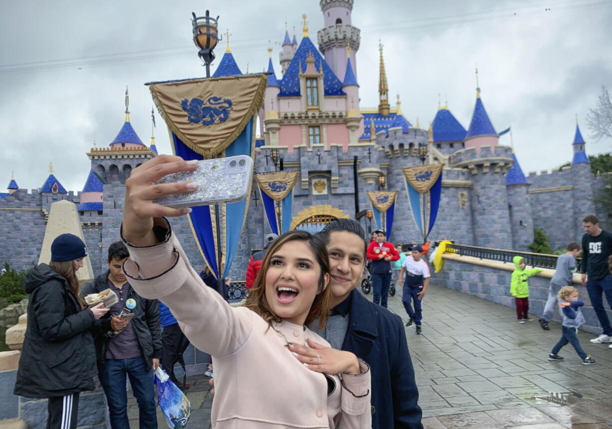 FILE - In this March 13, 2020, file photo, Katherine Quezada shows off her engagement ring as she takes a selfie with her new fiance, Fernando Carranza, in front of Sleeping Beauty Castle the during the last day before Disneyland closes because of the COVID-19 coronavirus outbreak, in Anaheim, Calif. Carranza proposed to Quezada in front of the castle earlier that day. Disneyland Park and Disney California Adventure park will reopen to visitors on Friday, April 30, 2021.