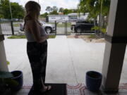 """Nicole Russell looks out from her porch, Friday, March 12, 2021, in Kendall, Fla. Because of the pandemic, Nicole because fearful of leaving her home and retreated to her bedroom for days at a time. While some felt restricted by the confinement of home """"caves"""", others found a sense of safety and comfort, becoming increasingly accustomed to the isolation."""