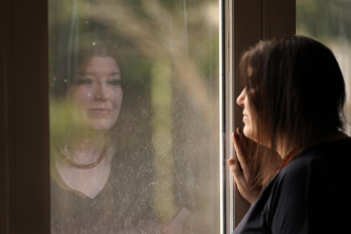 Keri Wegg is reflected in a sliding glass door as she looks outside her home in Westfield, Ind., on Monday, March 22, 2021. The Indiana nurse came down with COVID-19 in the summer of 2020; her condition spiraled downward, and her life was saved only by grace of a double lung transplant. The road to normal is a long one, but she's bolstered by the love and support of her husband and sons, and by her own indomitable spirit.