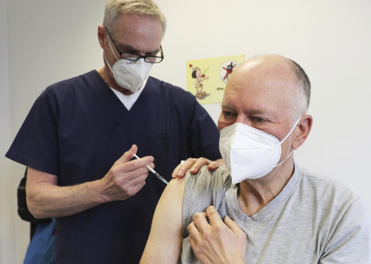Manfred Haas, right, receives the AstraZeneca vaccine against the COVID-19 disease from his family doctor Oliver Funken in Rheinbach, Germany, Tuesday, April 6, 2021. In German federal state North Rhine-Westphalia, Corona vaccinations have started in GP surgeries.