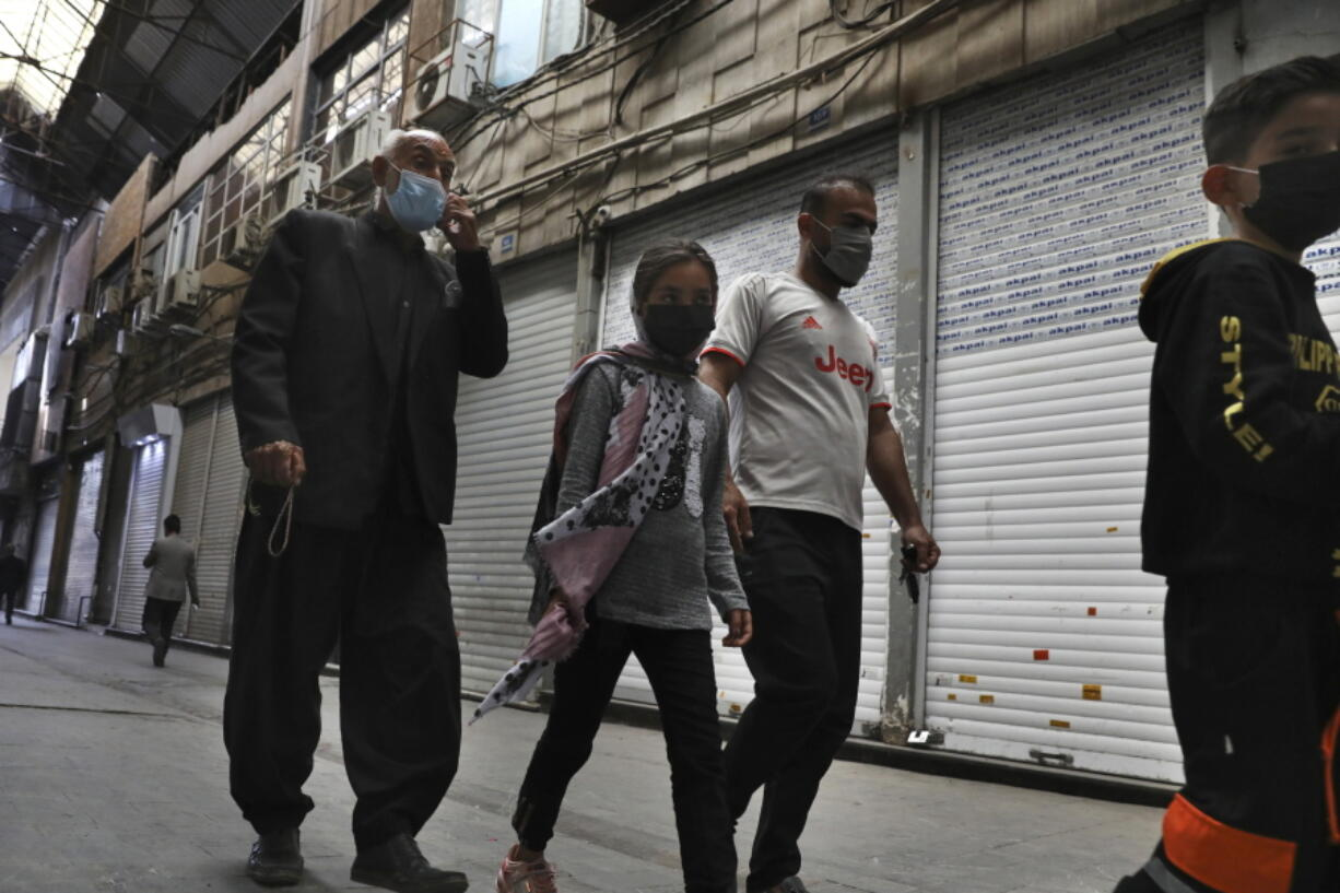 People walk through closed Tehran's Grand Bazaar, Iran, Saturday, April 10, 2021. Iran on Saturday imposed partial lockdown on businesses in major shopping centers as well as intercity travels through personal cars in major cities including capital Tehran as it struggles with the worst outbreak of the coronavirus in the Mideast region.