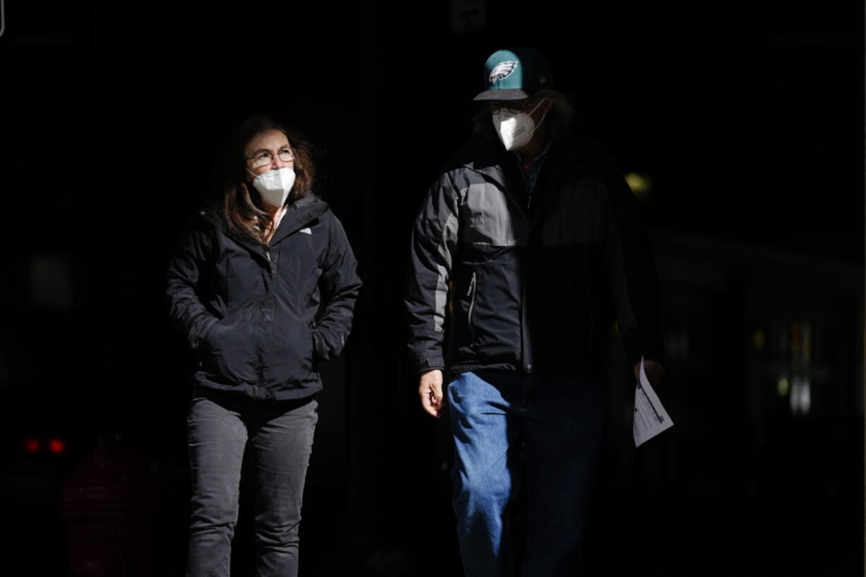 FILE - In this Wednesday, March 3, 2021 file photo, people wearing face masks as a precaution against the coronavirus walk through a shaft of light on a street in Philadelphia. On Tuesday, April 27, 2021, U.S. health officials say fully vaccinated Americans don't need to wear masks outdoors anymore unless they are in a big crowd of strangers, and those who are unvaccinated can go without a face covering outside in some cases, too.