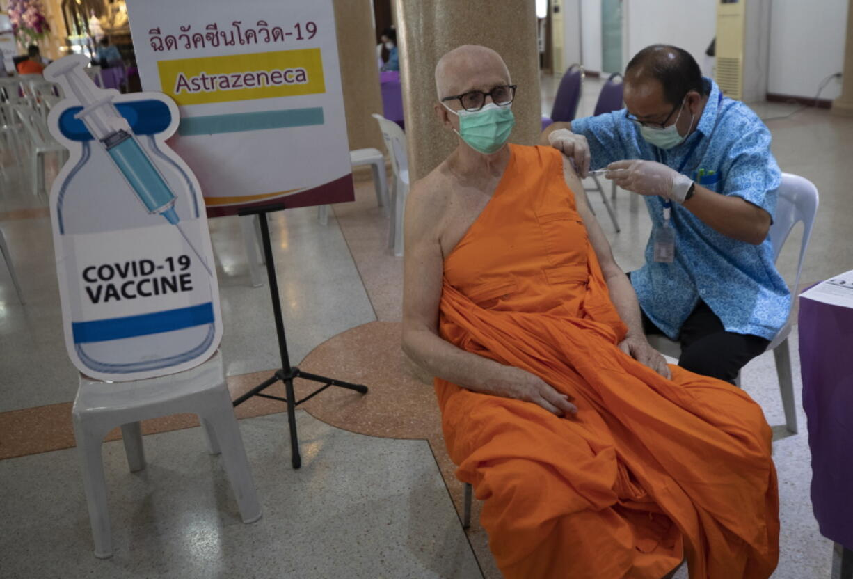 A health worker administers a dose of the AstraZeneca COVID-19 vaccine to a Buddhist monk at Nak Prok Temple in Bangkok, Thailand, Friday, April 9, 2021.