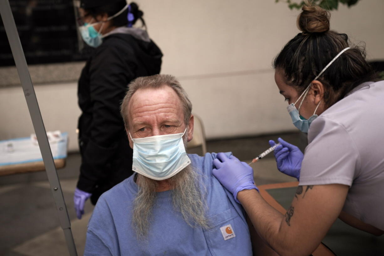 FILE - In this Feb. 3, 2021, file photo, EMT Rachel Bryant, right, administers a COVID-19 vaccine to a homeless man in the courtyard of the Midnight Mission in Los Angeles. Homeless Americans who have been left off priority lists for coronavirus vaccinations - or even bumped aside as states shifted eligibility to older age groups - are finally getting their shots as vaccine supplies increase.  (AP Photo/Jae C.