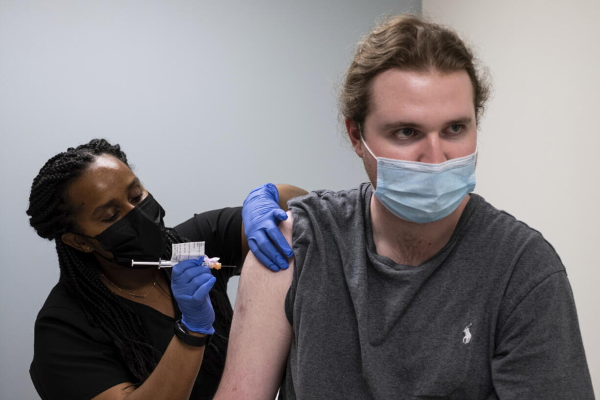 """Cole Smith receives a Moderna variant vaccine shot from clinical research nurse Tigisty Girmay at Emory University's Hope Clinic, on Wednesday afternoon, March 31, 2021, in Decatur, Ga. Smith, who received Moderna's original vaccine a year ago in a first-stage study, said returning wasn't a tough decision. """"The earlier one, it was a great success and, you know, millions of people are getting vaccinated now. ..."""