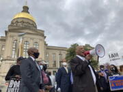FILE - In this March 25, 2021, file photo African Methodist Episcopal Church Bishop Reginald Jackson announces a boycott of Coca-Cola Co. products outside the Georgia Capitol n Atlanta.