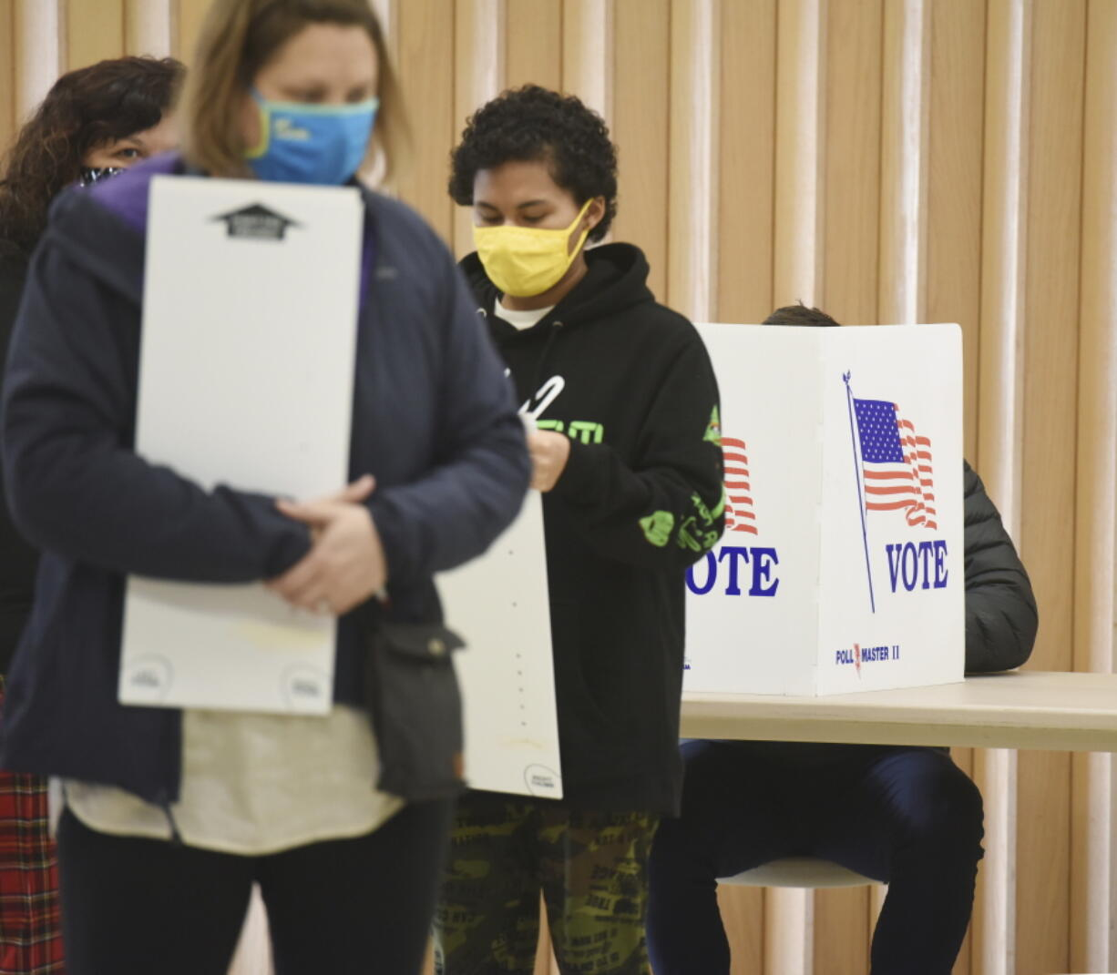 FILE - In this Nov. 3, 2020 file photo, residents wear masks as they vote at the Zion St. Joe United Church of Christ on Election Day, in St. Joseph, Mich. The leaders of three-dozen major Michigan-based companies, including General Motors and Ford, announced Tuesday, April 13, 2021, their opposition to Republican-sponsored election bills that would make it harder to vote in Michigan and other states.