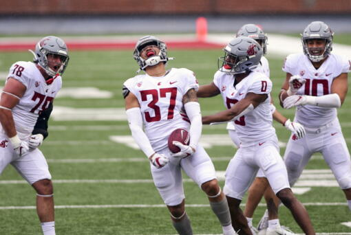 Washington State linebacker Justus Rogers (37) celebrates with with defensive back Jaylen Watson (0) and others after intercepting a pass by quarterback Jarrett Guarantano during the first quarter of the NCAA college football team's spring game Saturday, April 24, 2021, in Pullman, Wash. (Pete Caster/Lewiston Tribune via AP)