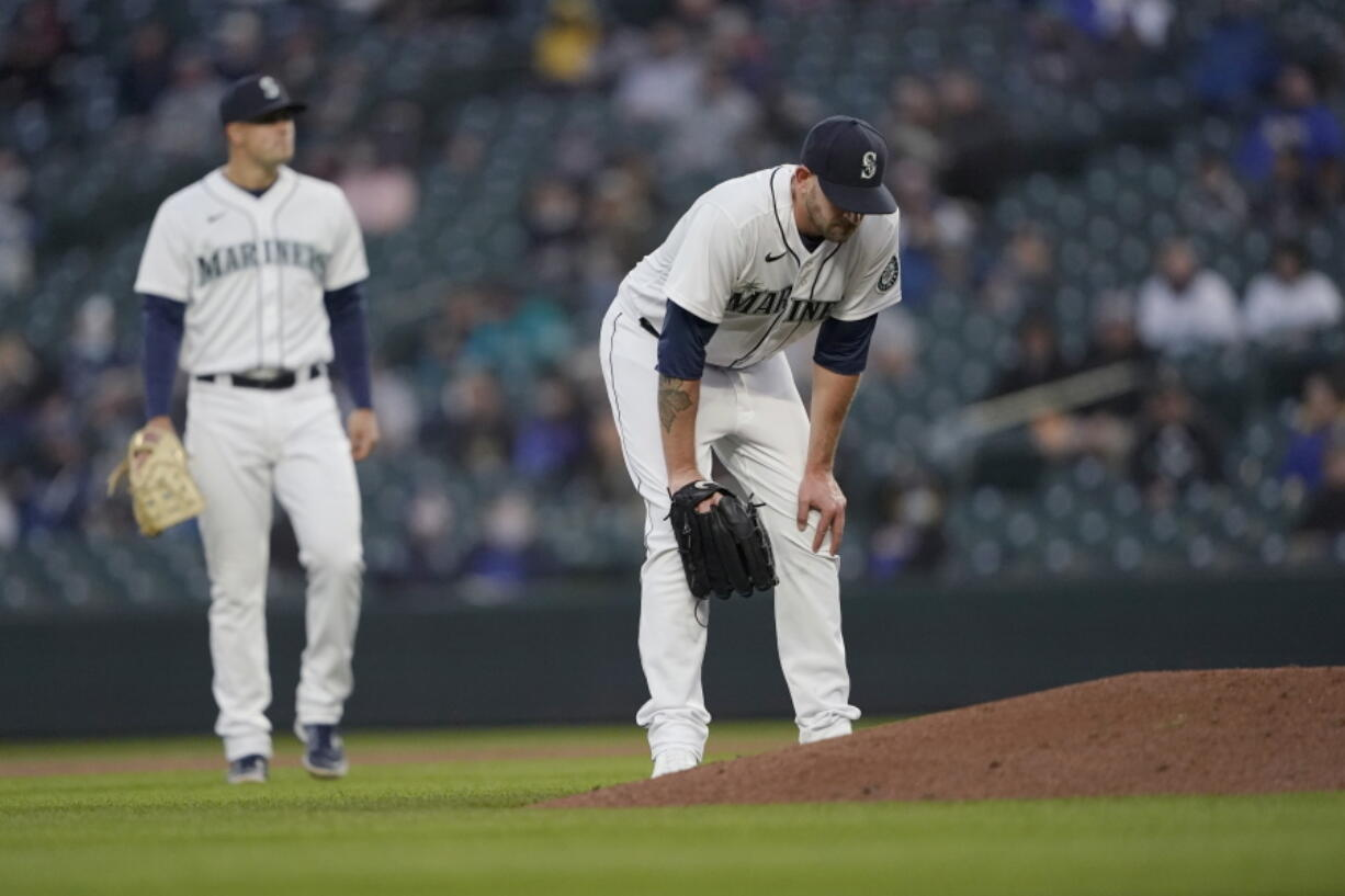 Seattle Mariners starting pitcher James Paxton, right, reacts near the mound after experiencing an injury during the second inning of a baseball game against the Chicago White Sox, Tuesday, April 6, 2021, in Seattle. Paxton left the game and the White Sox won 10-4. (AP Photo/Ted S.