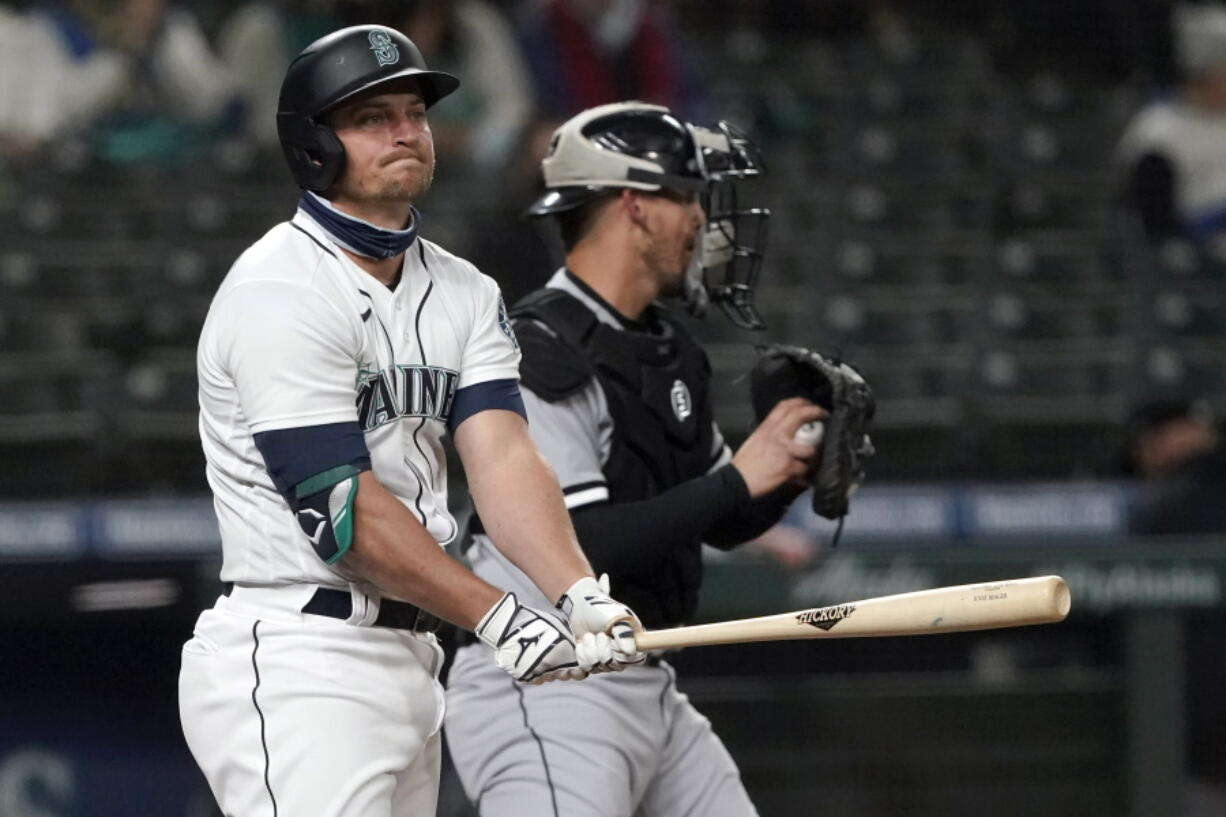Seattle Mariners' Kyle Seager reacts after striking out swinging to end the third inning as Chicago White Sox catcher Yasmani Grandal holds the ball during a baseball game, Monday, April 5, 2021, in Seattle. (AP Photo/Ted S.