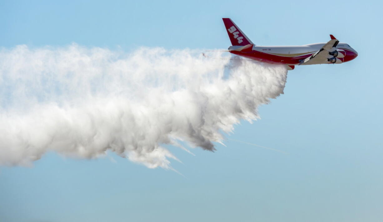 FILE - In this May 5, 2016, file photo, a Boeing 747-400 Global SuperTanker drops half a load of its 19,400-gallon capacity during a ceremony at Colorado Springs, Colo. The world's largest firefighting plane has been shut down just as Western states prepare for a wildfire season that fire officials fear could be worse than the average year. Tara Lee, a spokeswoman for Washington Gov.