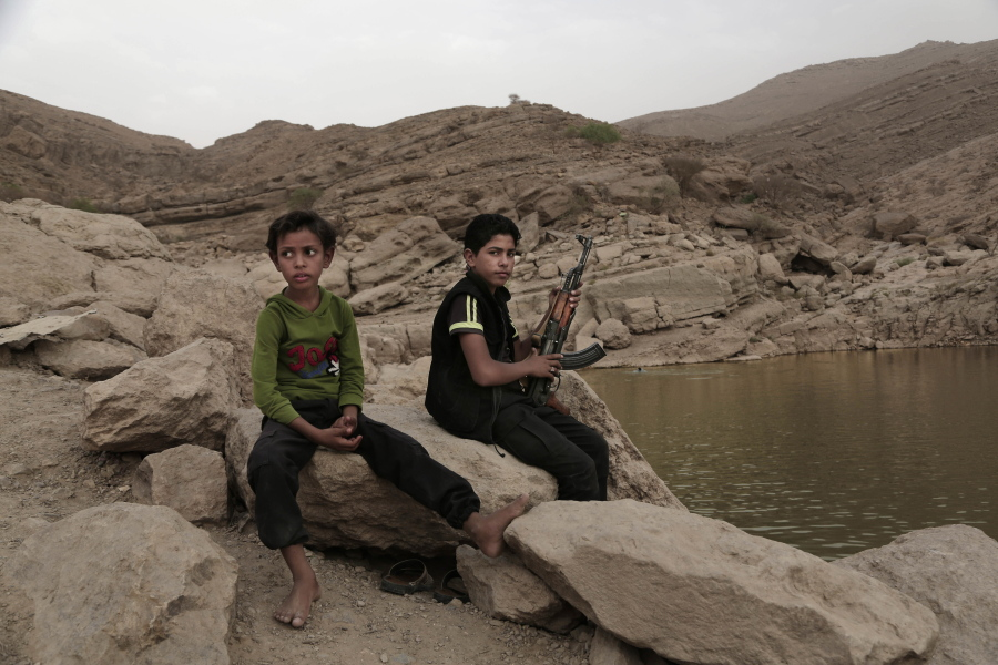 FILE - In this July 30, 2018, file photo, a 17-year-old boy holds his weapon at the dam in Marib, Yemen. The battle for the ancient desert city has become key to understanding wider tensions now inflaming the Middle East and the challenges facing any efforts by President Joe Biden's administration to shift U.S. troops out of the region.