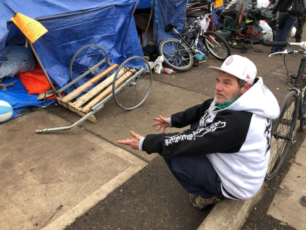 James Wilbur speaks to a reporter Dec. 17, 2019, in Salem, Ore., after he and other homeless people camping on a street were notified that they must leave. Oregon lawmakers passed a bill that will make it easier and quicker for communities to create emergency shelters and temporary housing.