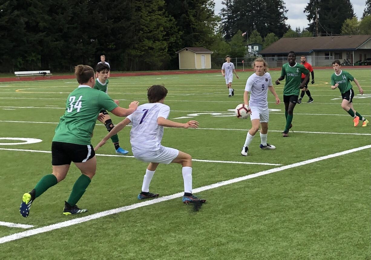 Columbia River's Alexander Harris (7) shields off a Tumwater defender after a pass from teammate Logan Simmons (9) during the 2A boys soccer district championship match on Saturday at Tumwater High School.