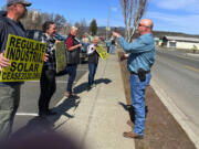 Dan Christopher, Klickitat County commissioner, talks with solar critics picketing across from the Goldendale Post Office.