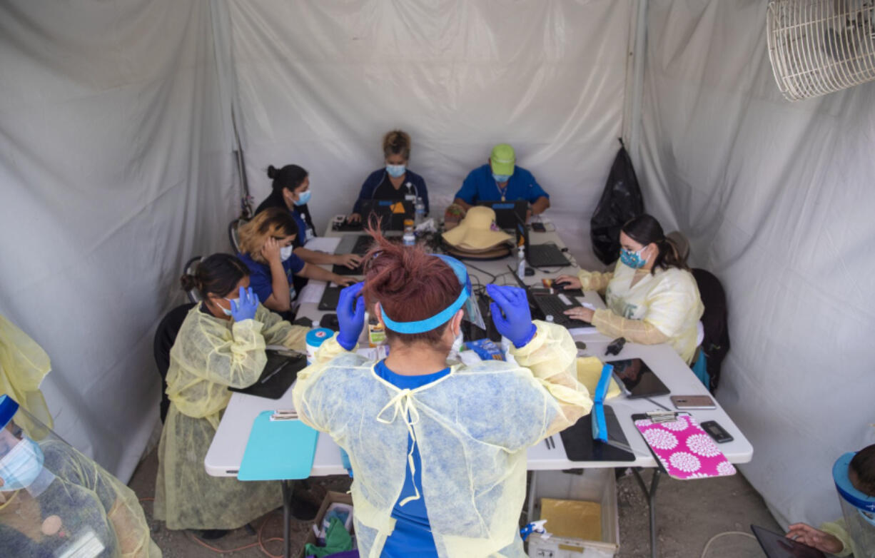 BOYLE HEIGHTS, CA - APRIL 29: Alta Med Health Services staff puts on PPE prior to COVID-19 testing on Wednesday, April 29, 2020 in Boyle Heights, CA.