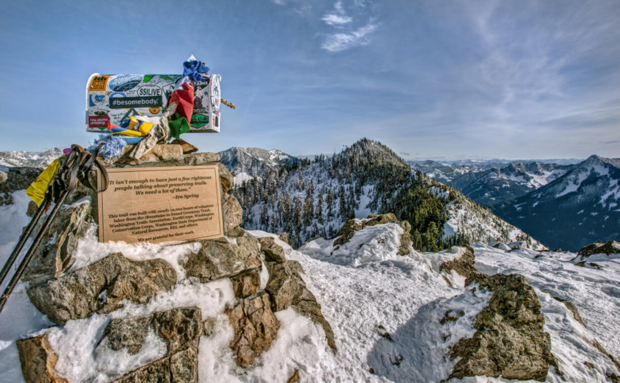 A Mailbox and Trekking Poles mark the Snowy Summit of Mailbox Peak in the Cascade Mountain Range.