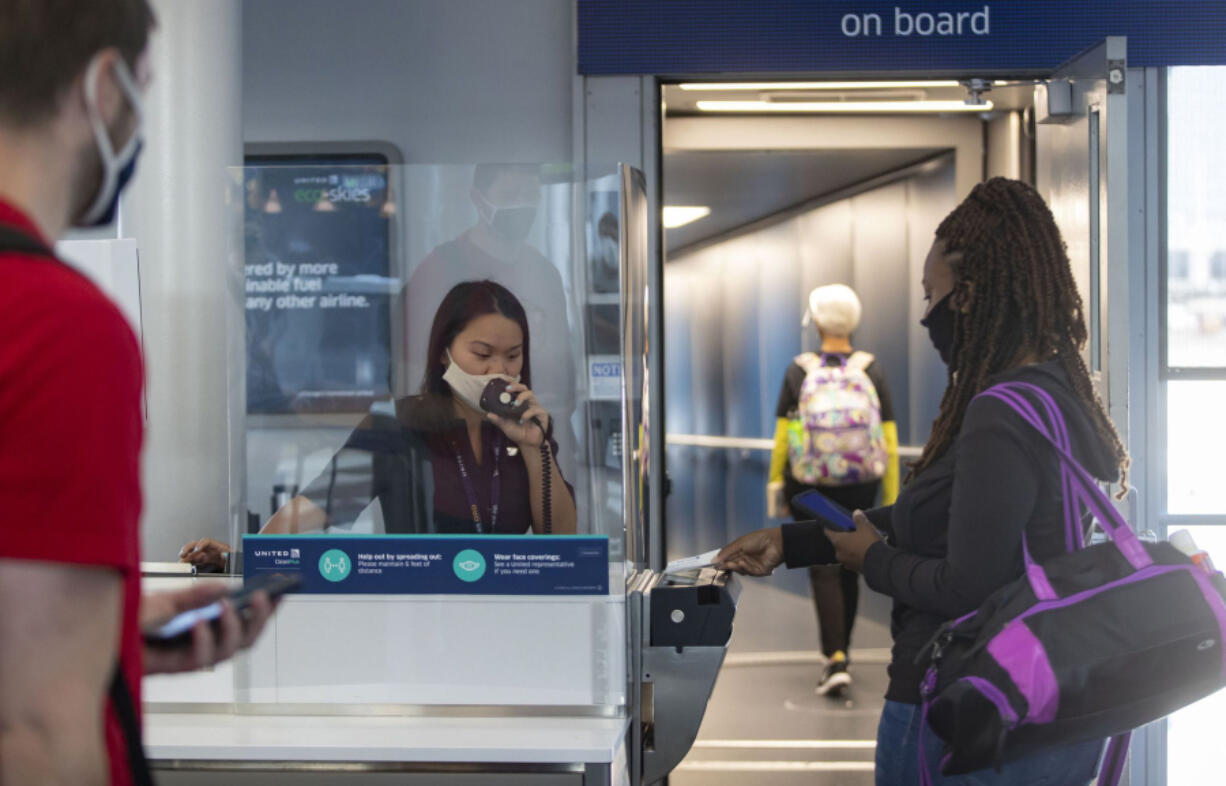United Airlines gate agent Emma Watt helps passengers scan their boarding passes for a flight to San Francisco at O'Hare International Airport on June 18.