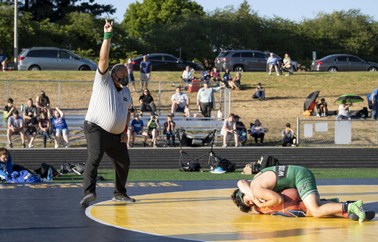 Washington Officials Association referee Lee Lofton calls two points for a takedown on Wednesday at Hudson's Bay High School. The dual meet between Woodland, Ridgefield and Hudson's Bay was believed by coaches to be among the first outdoor dual meets held in state history.