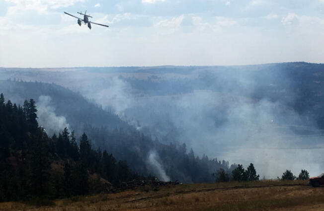 A Fire Boss plane - a fixed-wing aircraft used in wild land fire suppression - battles a wildfire in Eastern Washington in 2018.