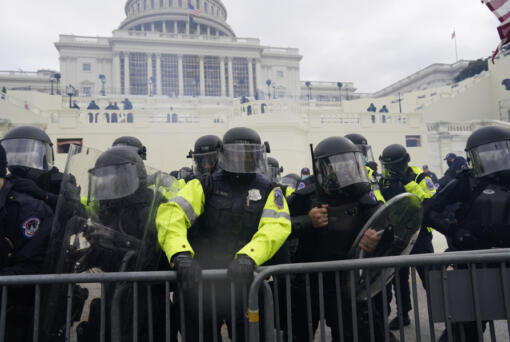 Police try to hold back protesters who gather to storm the Capitol and halt a joint session of the 117th Congress on Wednesday, Jan. 6, 2021, in Washington, D.C.