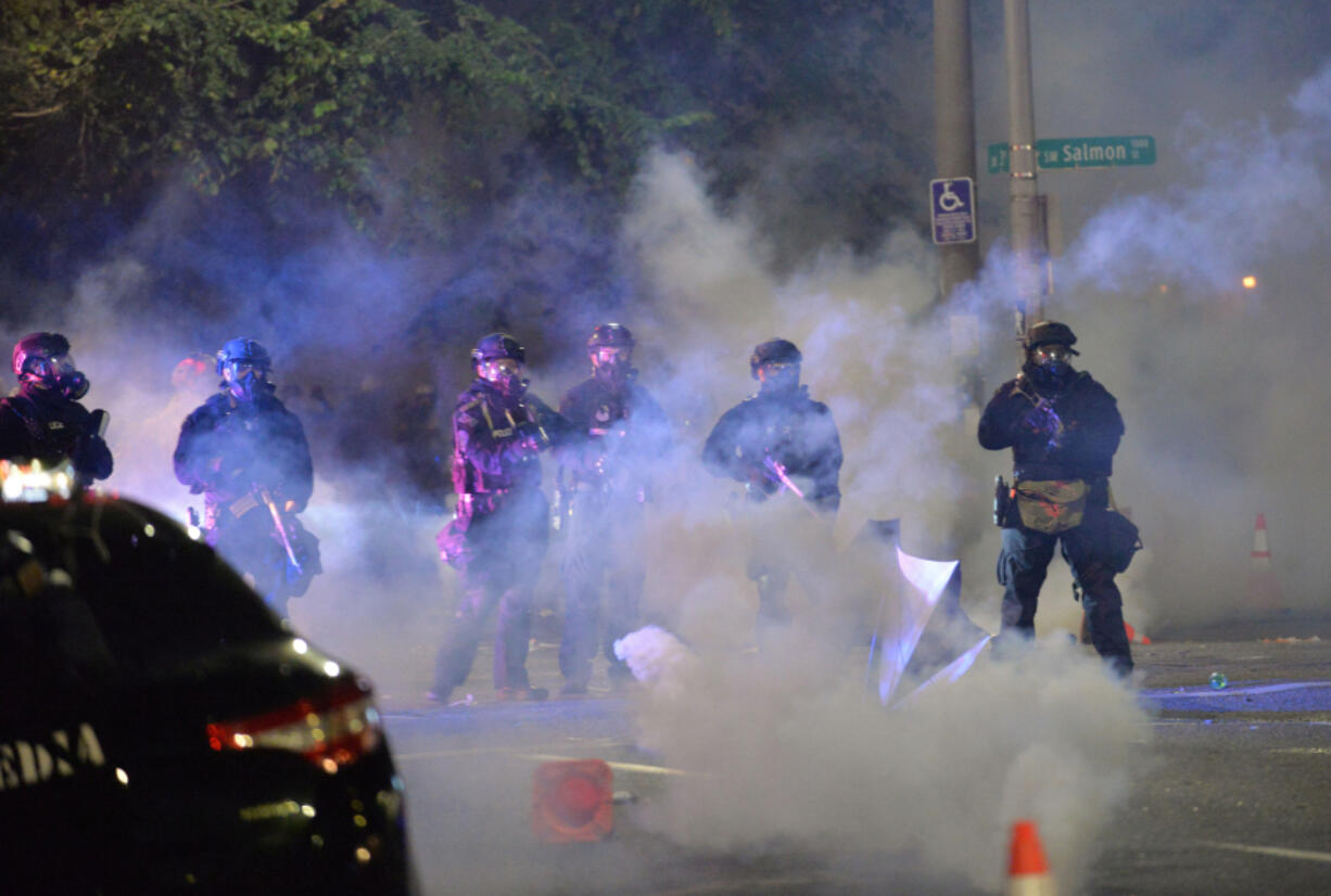 Security personnel stand in a cloud of tear gas in Portland, Oregon, early Sunday, July 26, 2020, as protests continued across the United States following the death of George Floyd.