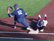 Skyview first baseman Brock Blakley (12) takes a throw as Camas baserunner Zach Blair safely dives back to the bag.