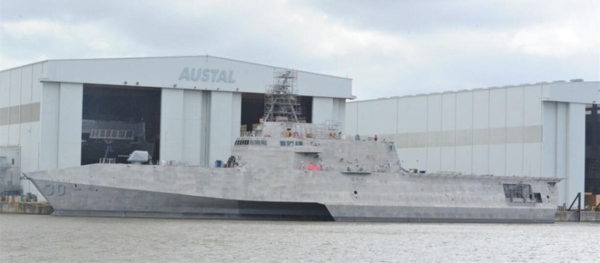 LCS-30, the future USS Canberra, is seen docked in front of the Austal USA facilities on the Mobile River where the company builds Littoral Combat Ships for the U.S. Navy.