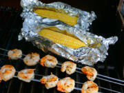 Grilled shrimp kabobs and grilled corn on the cob.